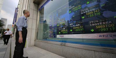 man looks at stocks in tokyo, japan